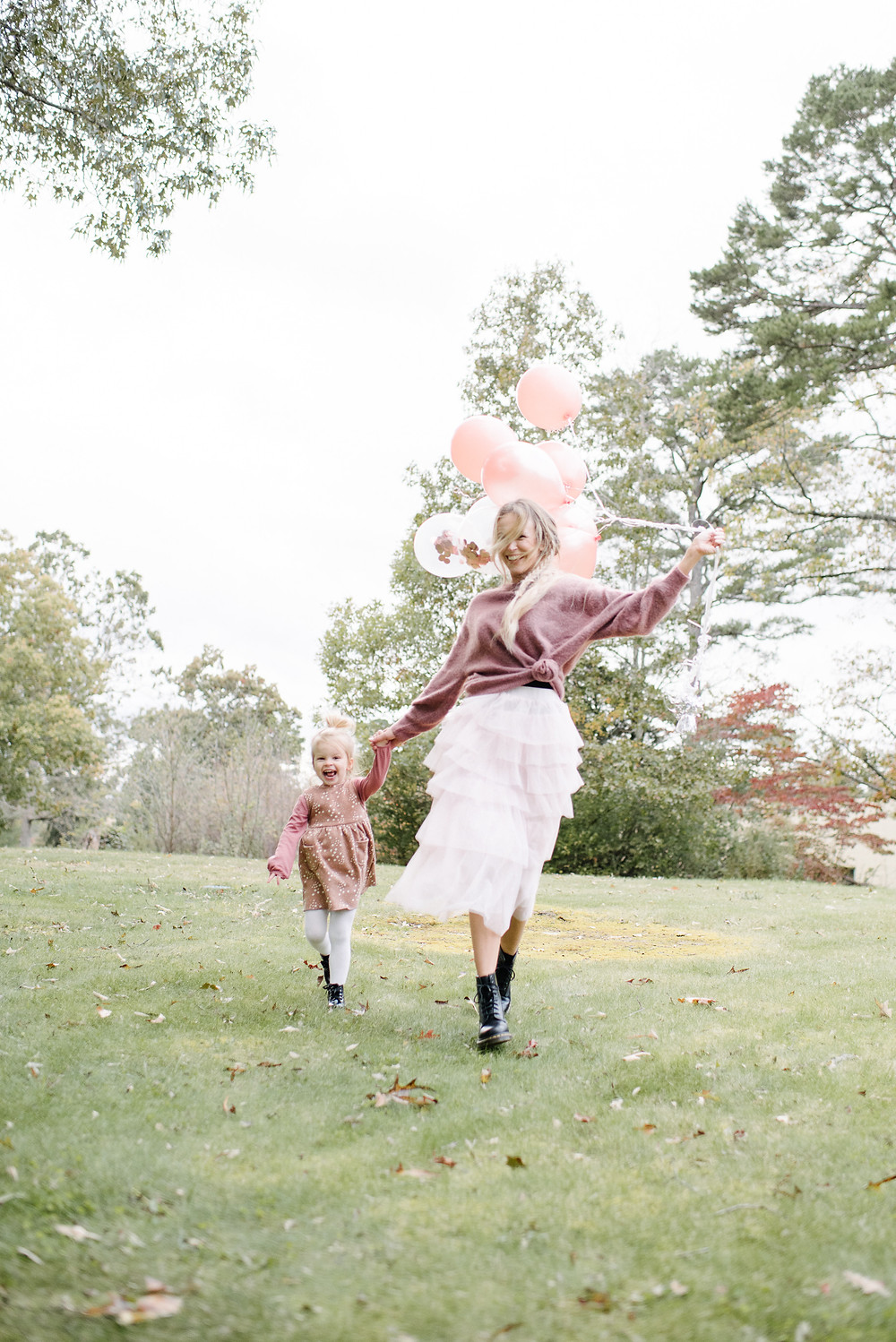 Mom and daughter running with pink balloons.