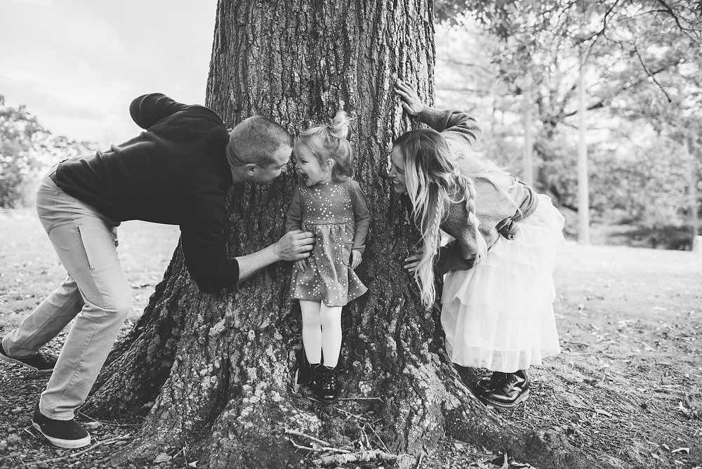 Family of three plays hide and seek behind tree.