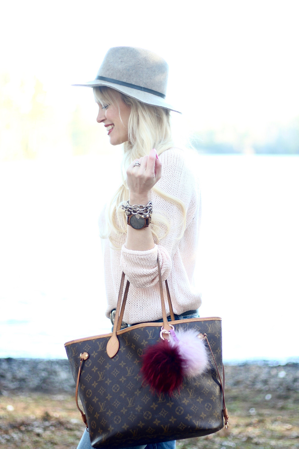 A young mom carries her Louis Vuitton diaper bag with colorful pom pom charms with her JORD Wood Watch on her wrist.