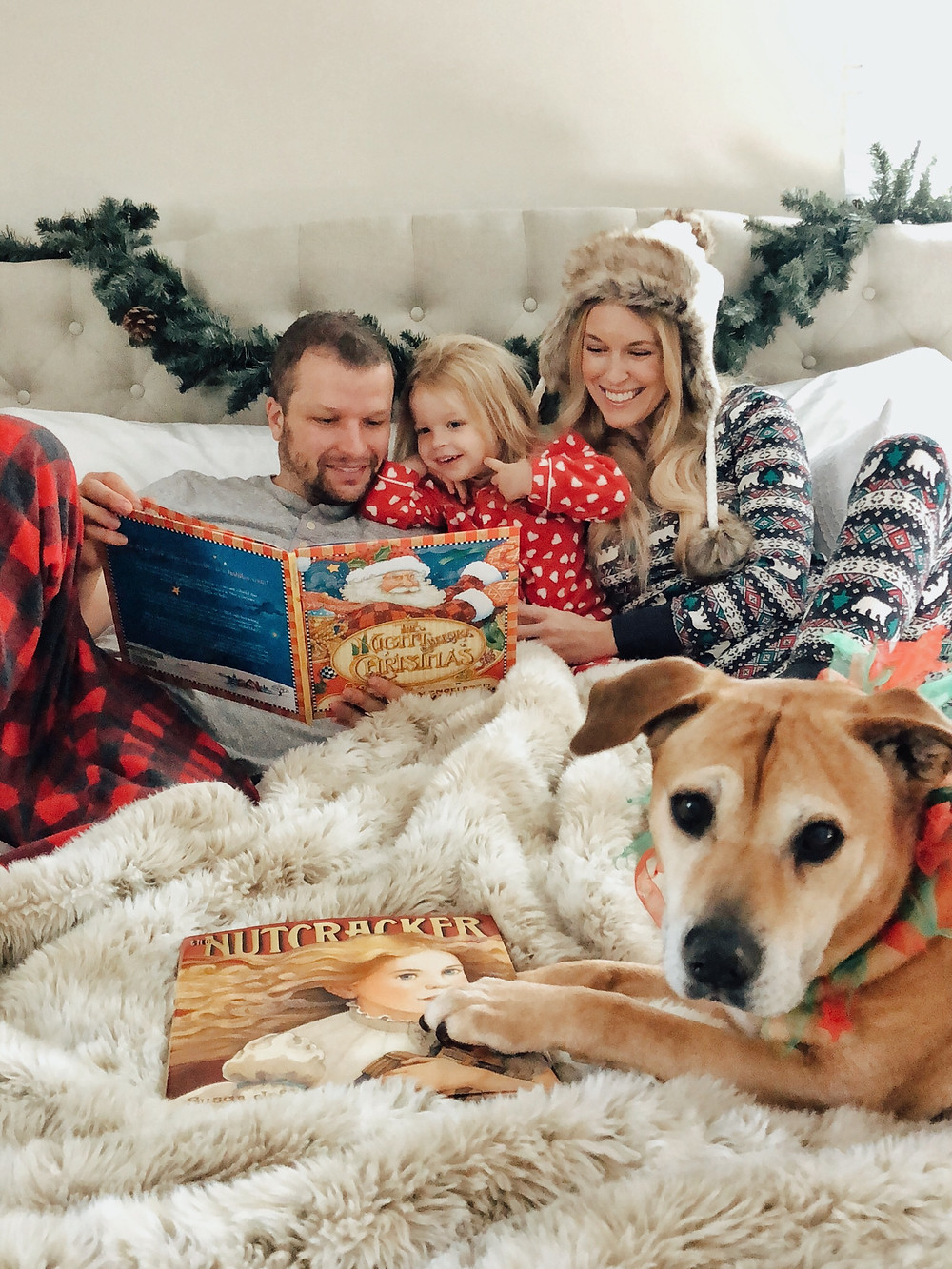 Family reads The Night Before Christmas snuggled in bed wearing coordinating Christmas pajamas.
