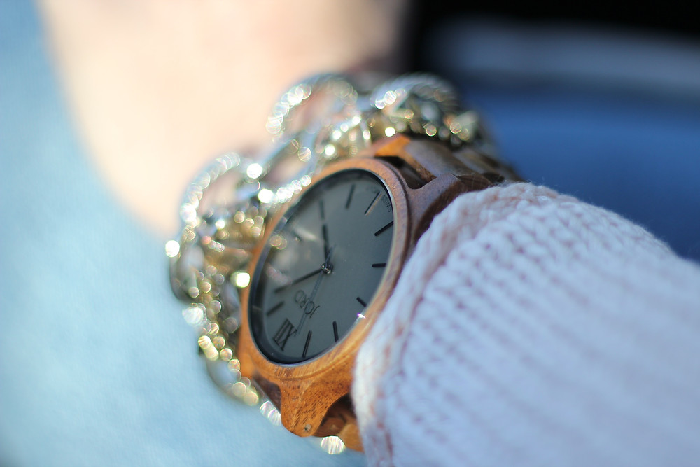 The Koa and Ash JORD Wood Watch styled on a woman's wrist with mixed metallic bracelets.