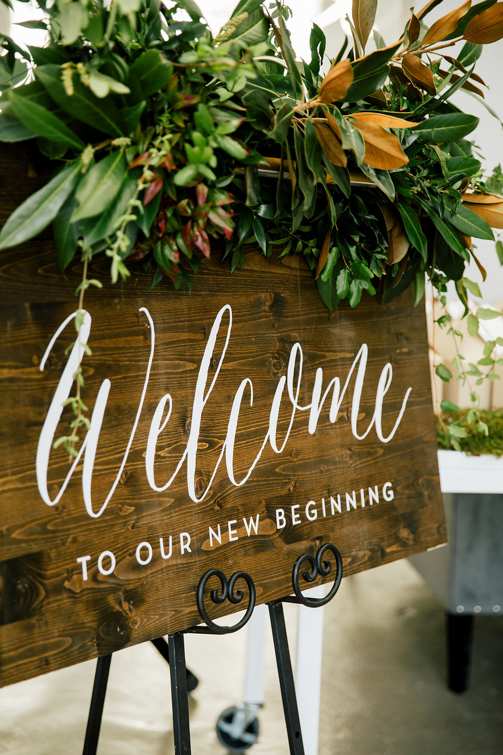 Handlettered welcome sign toppped with greenery for Engaged Wedding Studio Launch Party