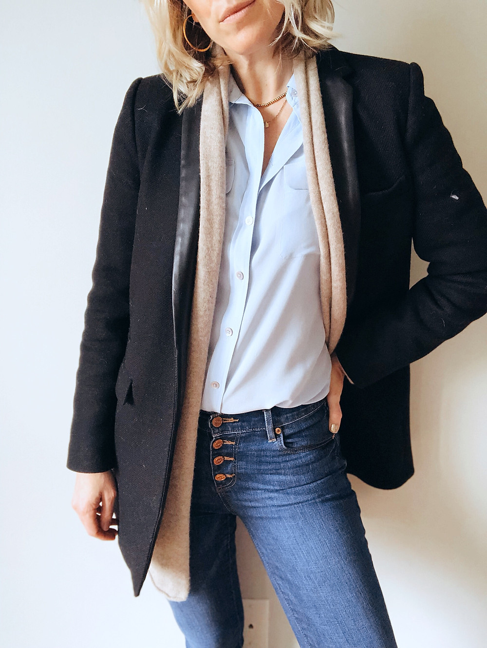 Black blazer layered ontop of tan cardigan, blue blouse, and button-front jeans.