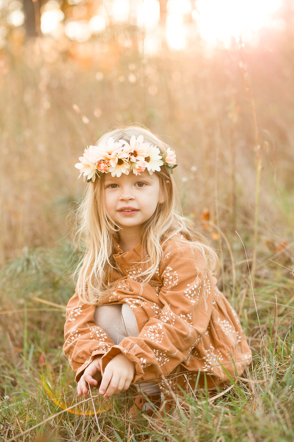 Little girl in a flower crown kneels down in a grassy field, London Adelaide family photography, Asheville family photographers, tips for planning family photos, lifestyle blog