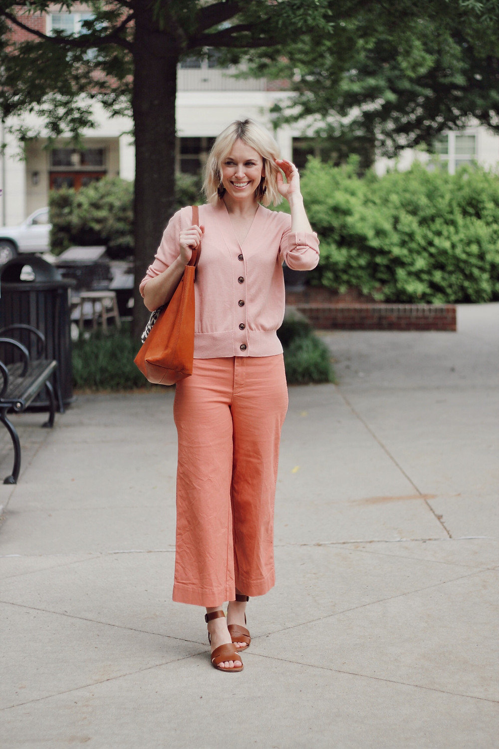 Woman wears spring outfit of pink cardigan, pink cropped pants, and tan sandals.