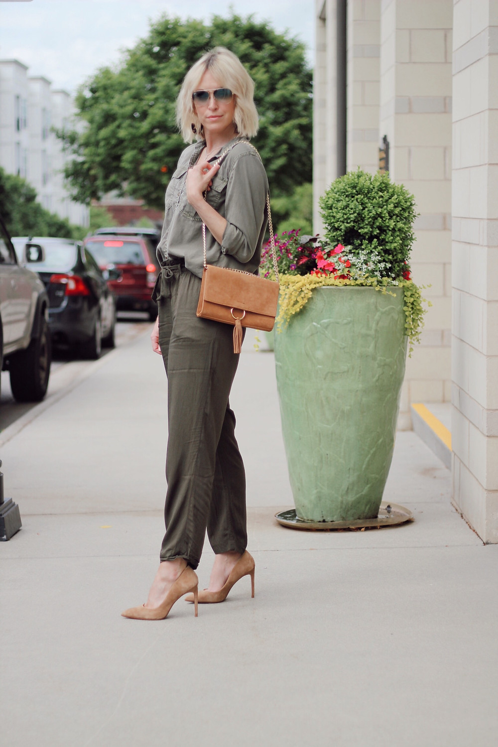 Woman wears spring monochromatic outfit olive cargo blouse olive pants.