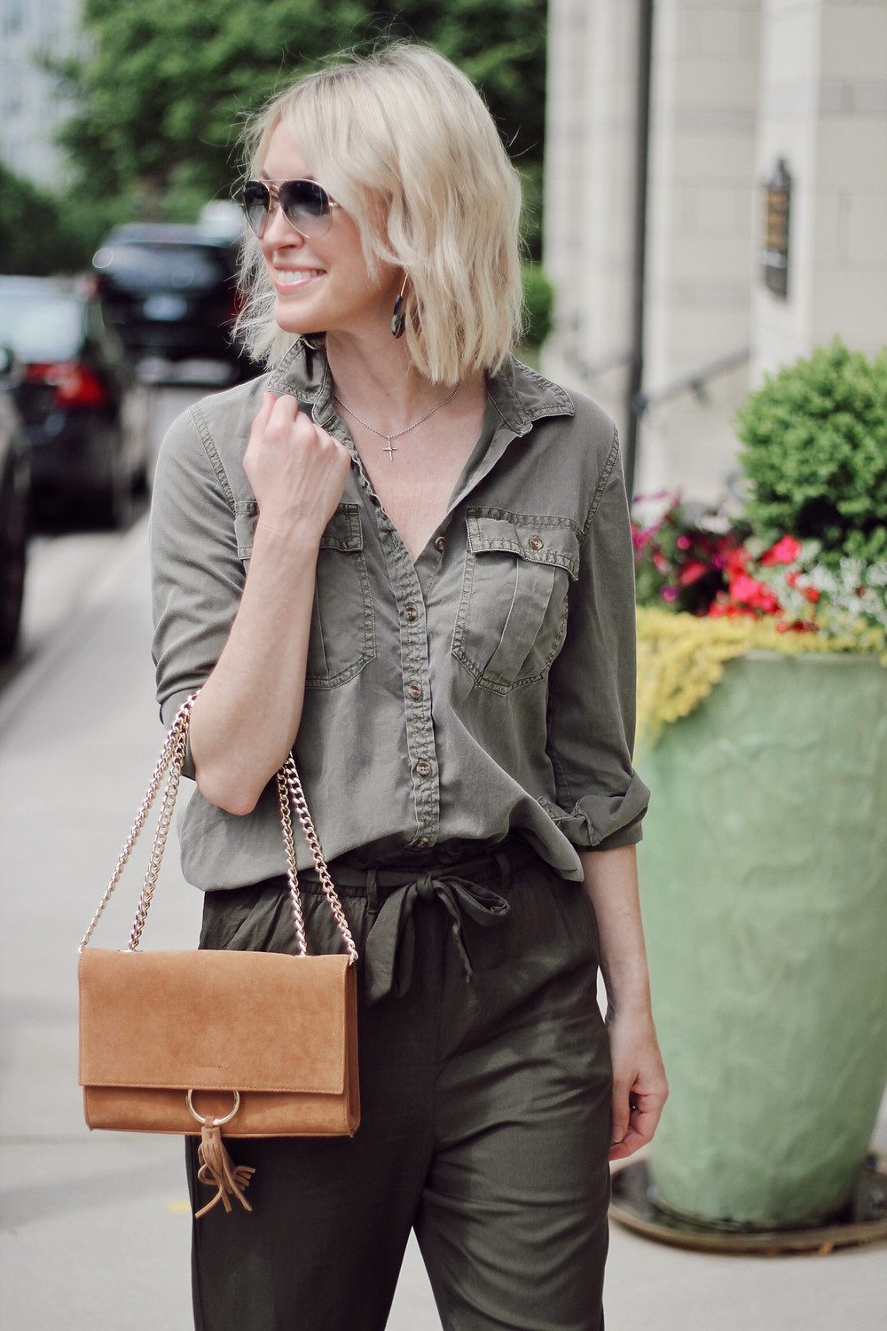 Woman wears olive cargo blouse tucked into olive paper bag waist trousers.