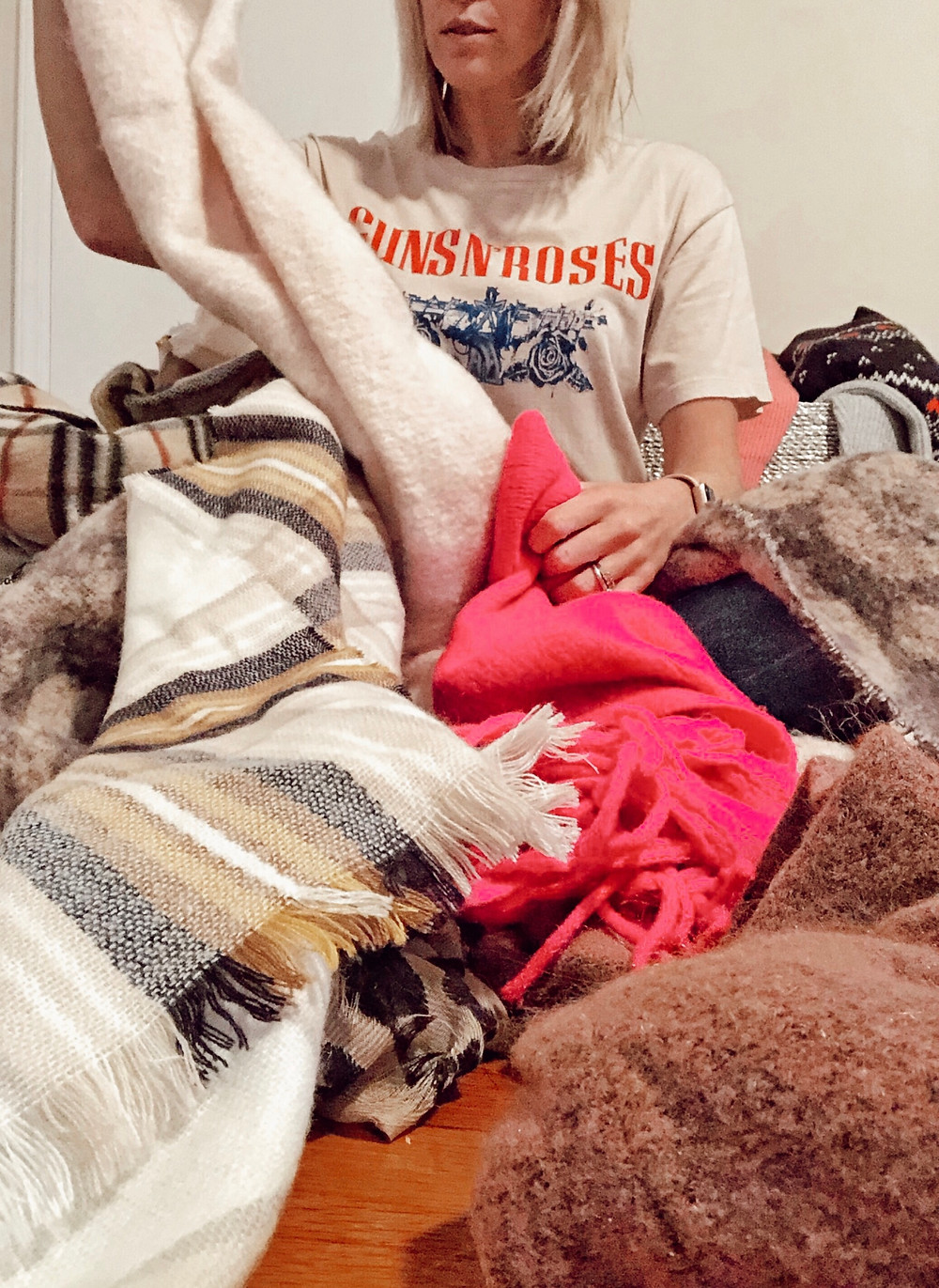 Woman sits on the floor buried under piles of winter scarves.