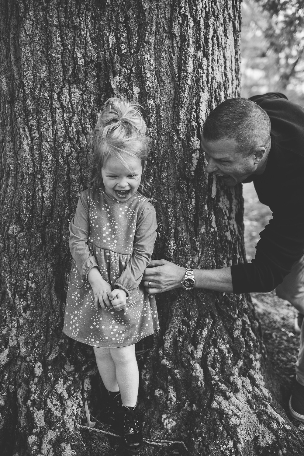 Dad surprises daughter behind tree trunk.