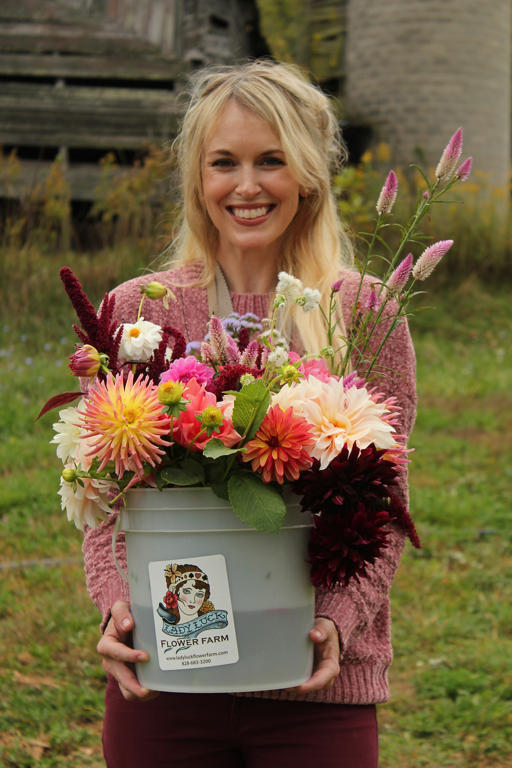 Brooke Williams smiles as she shows her bucket full of fresh flowers at Lady Luck Flower Farm in Asheville, NC.