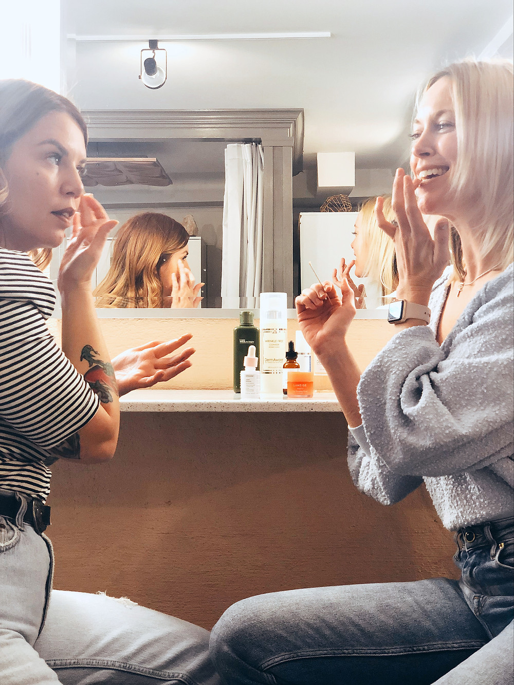 Two women applying skin care products in front of mirror.