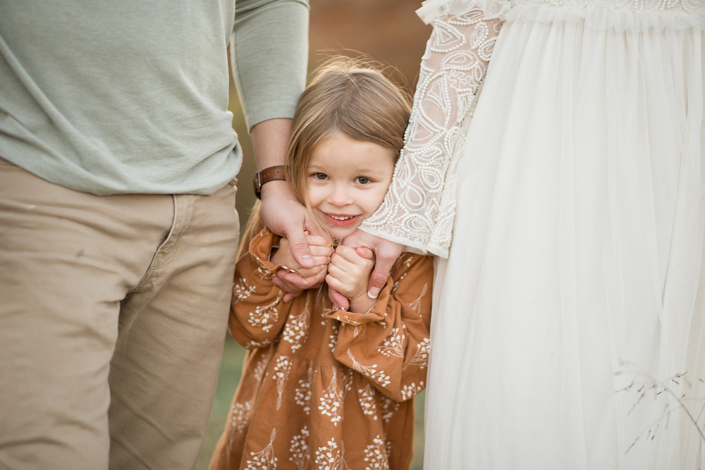 Little girl holds her parents hands tightly under her chin, London Adelaide family photography, Asheville family photographers, tips for planning family photos, lifestyle blog