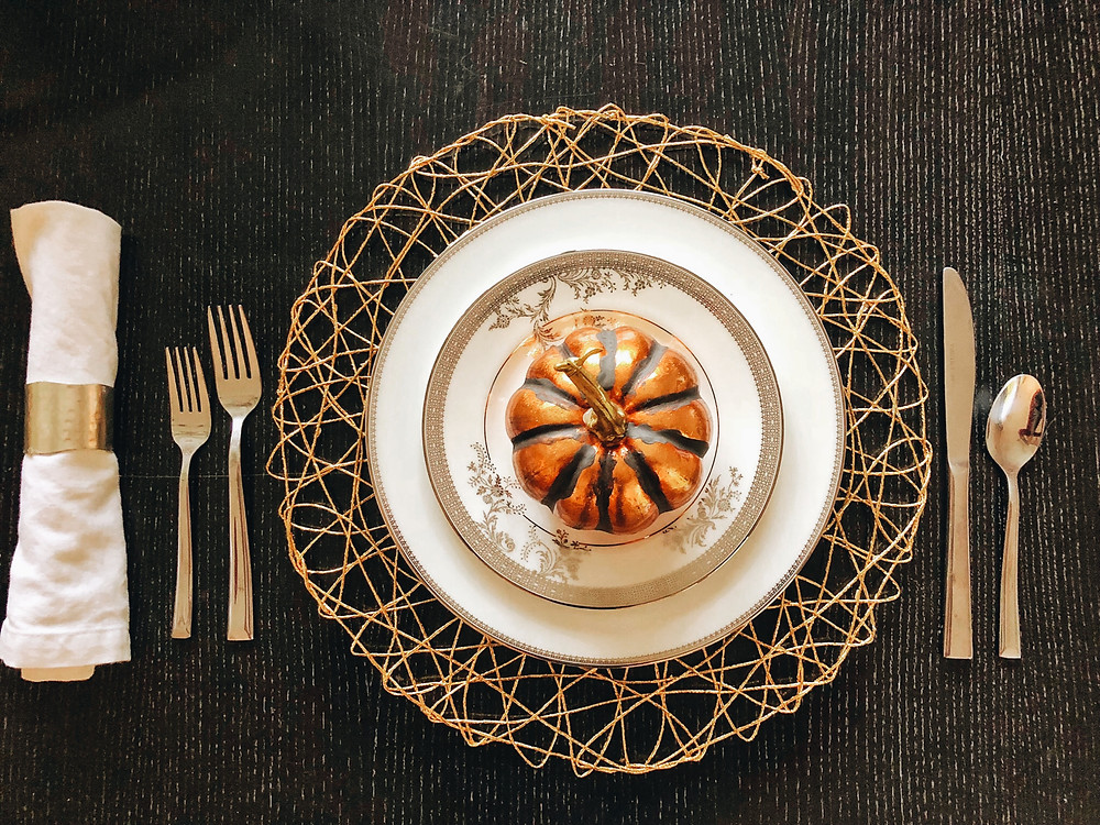 One glam place setting for Thanksgiving sits atop a gold wire placemat accented by a metallic orange pumpkin.