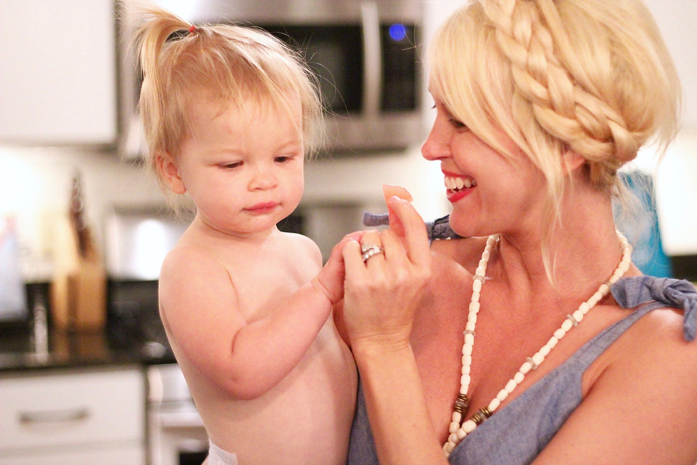 Mom blogger Brooke Williams feeds her daughter a piece of watermelon