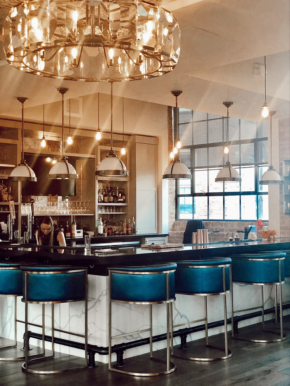 Blue bar stools, white pendant lights over Workshop Bar at Foundry Hotel Asheville NC