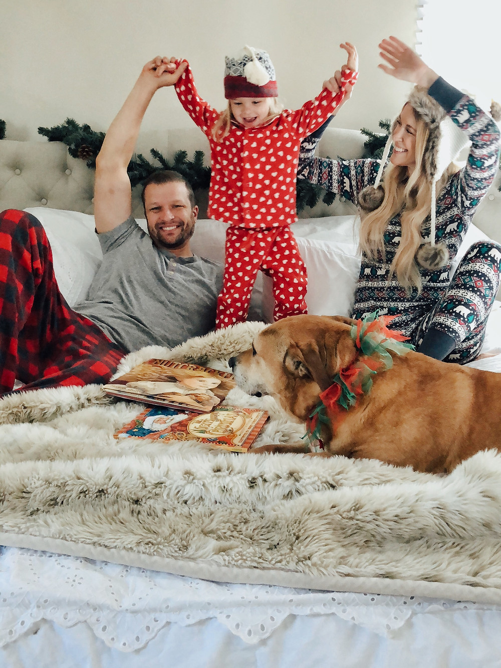 Toddler in heart print pajamas jumps on bed with parents and dog.