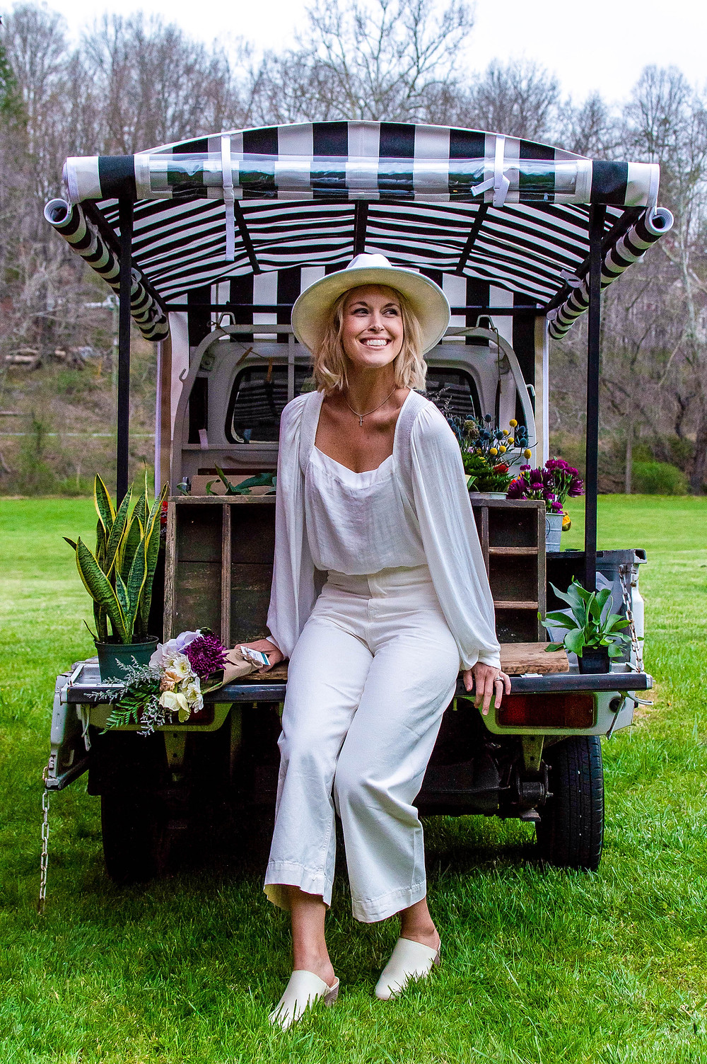 Woman wearing all white outfit sits on back of flower truck bed.