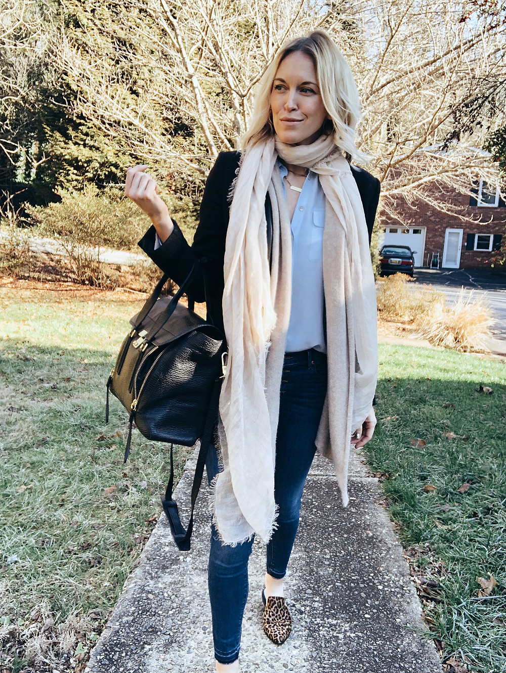 Layered winter neutrals outfit with ivory scarf, black blazer, light blue blouse, and blue jeans.