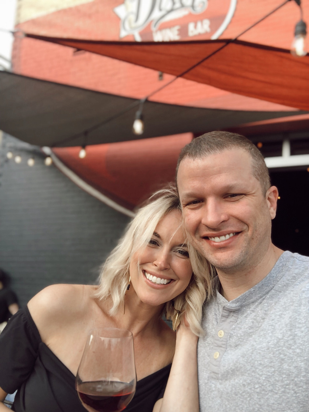 Couple smile in front of red awning at District Wine bar