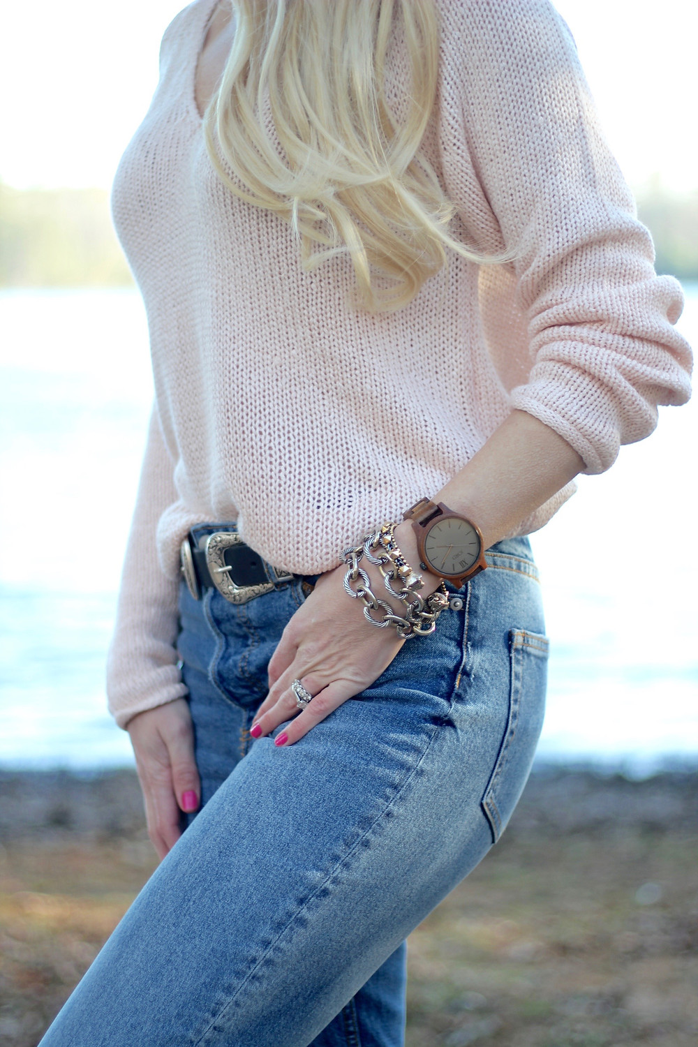 A young mom in a blush pink sweater casually styles her western belt and girlfriend jeans with her JORD Wood Watch.