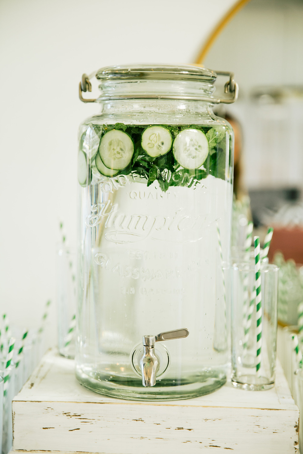 Cucumber Basil infused water urn surrounded by glases with green striped straws