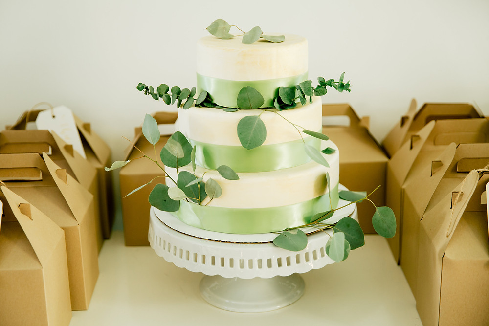Three-tiered cake with greenery and green ribbon sits amongst gift boxes