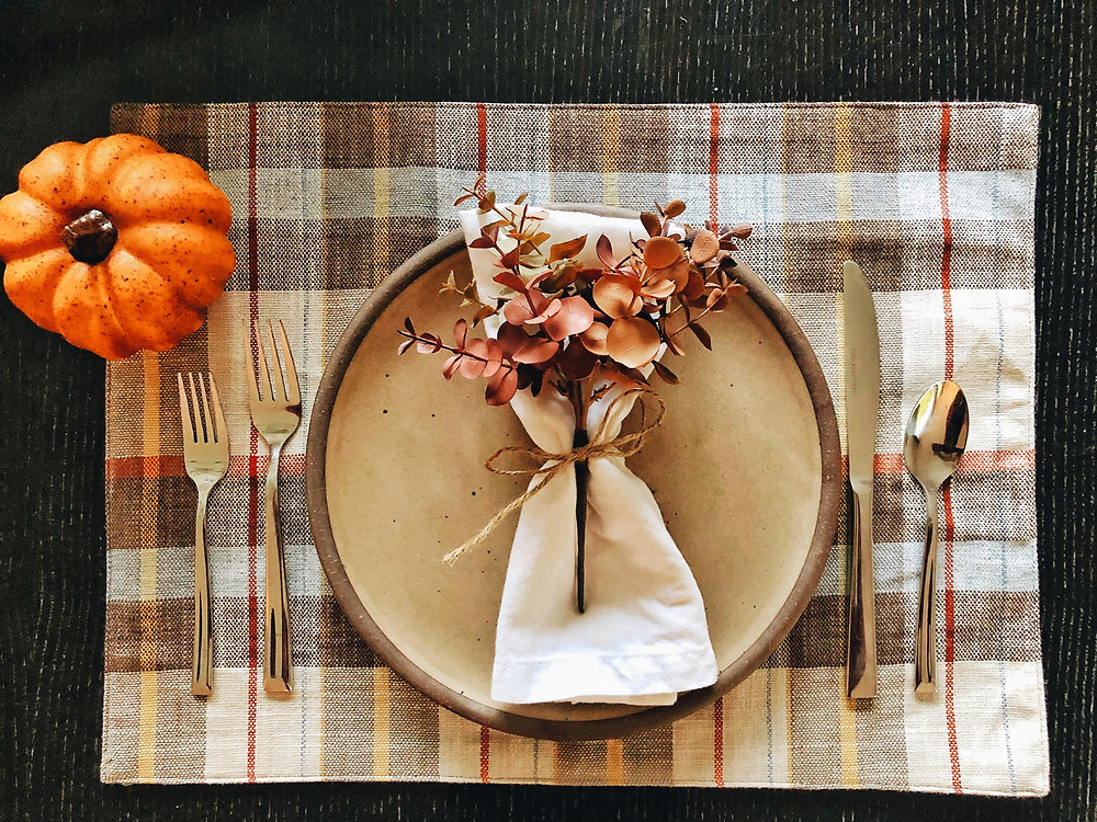 One place setting sits atop a plaid placemat with pumpkin and succulent accents.
