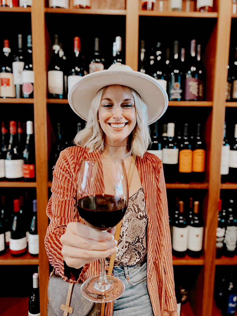 Woman cheers a glass of red wine at the camera at Santé Wine Bar and Tap Room in the Grove Arcade in Asheville North Carolina. Local travel guide and lifestyle blogger The Tony Townie.