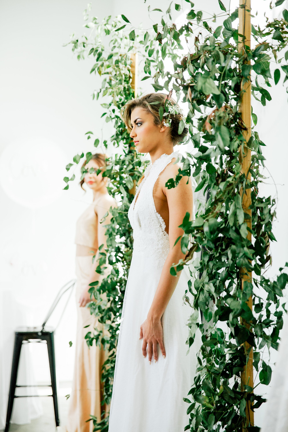 Models in wedding gowns stand between greenery-laden posts