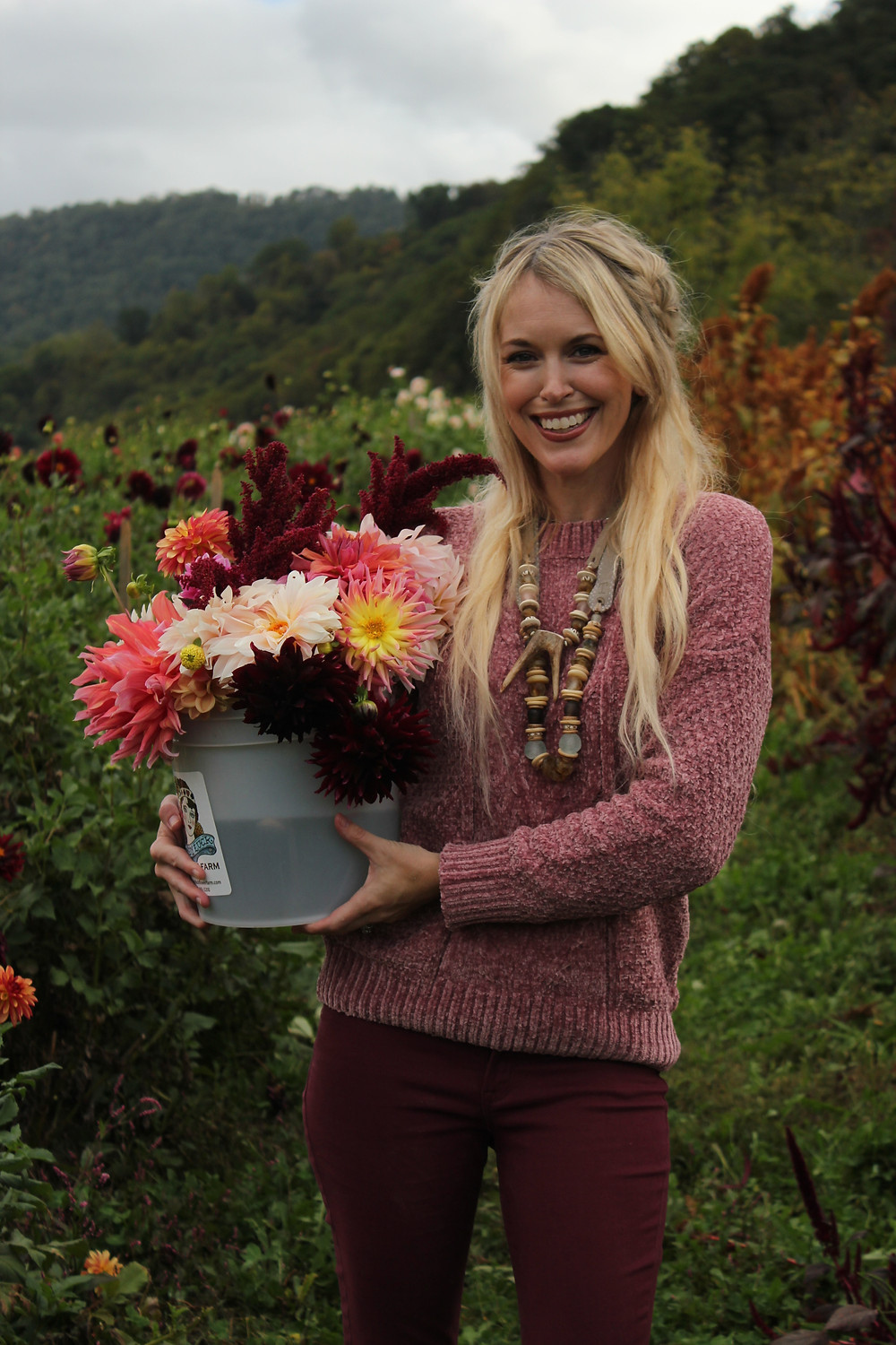 Brooke holds a bucket full of pink and red flowers at Lady Luck Flower Farm in Asheville, NC.