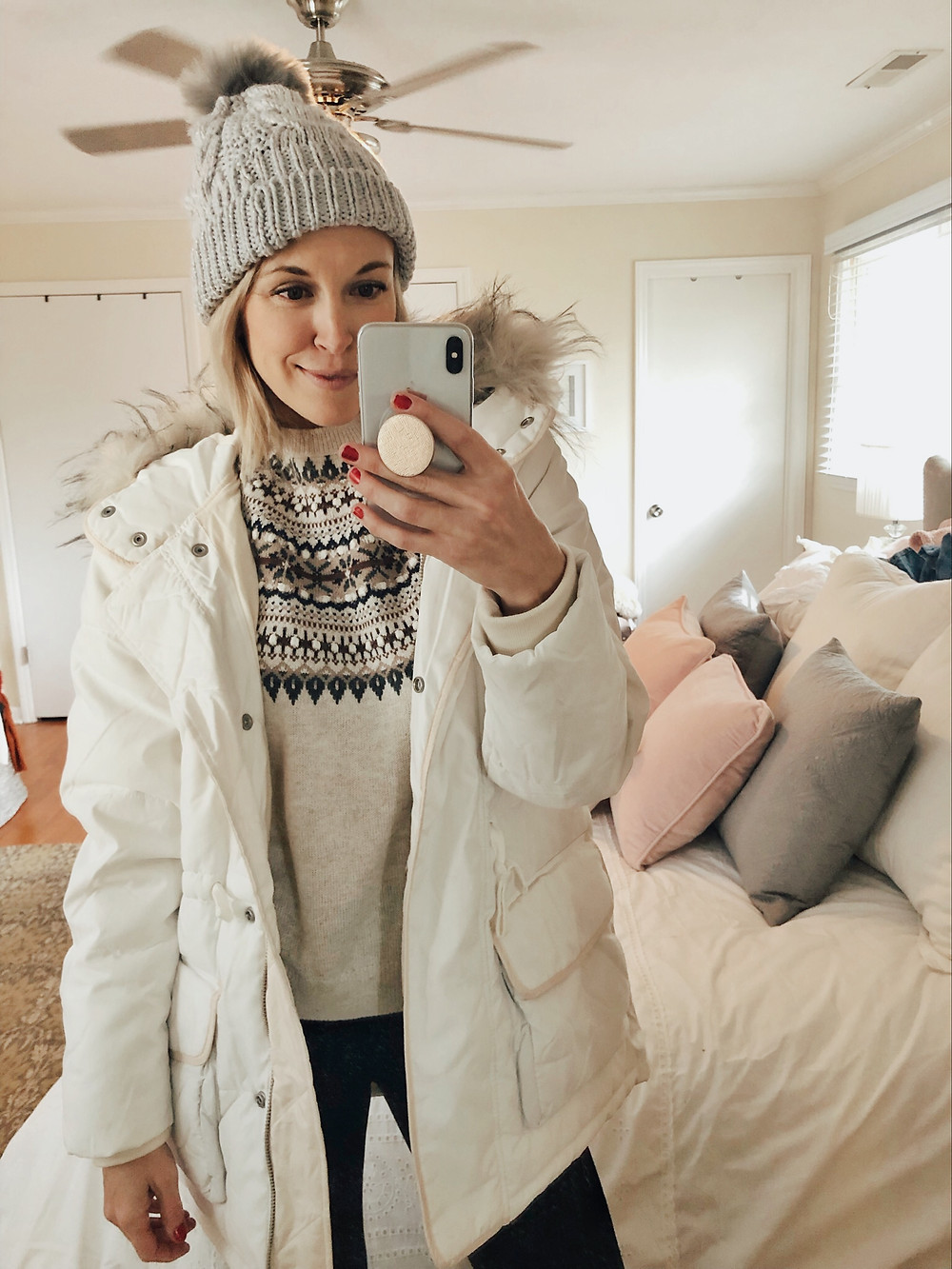 Brooke Williams (The Tony Townie) layers a white parka jacket and gray knit beanie over her fair isle sweater.