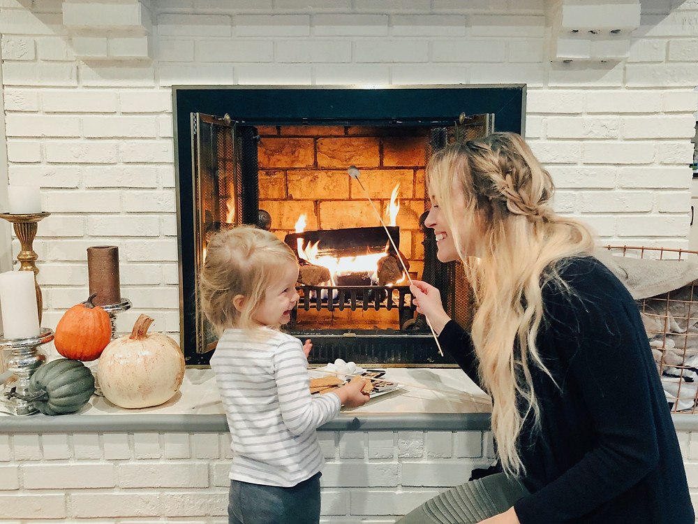 Family roasts s'mores by a white brick fireplace