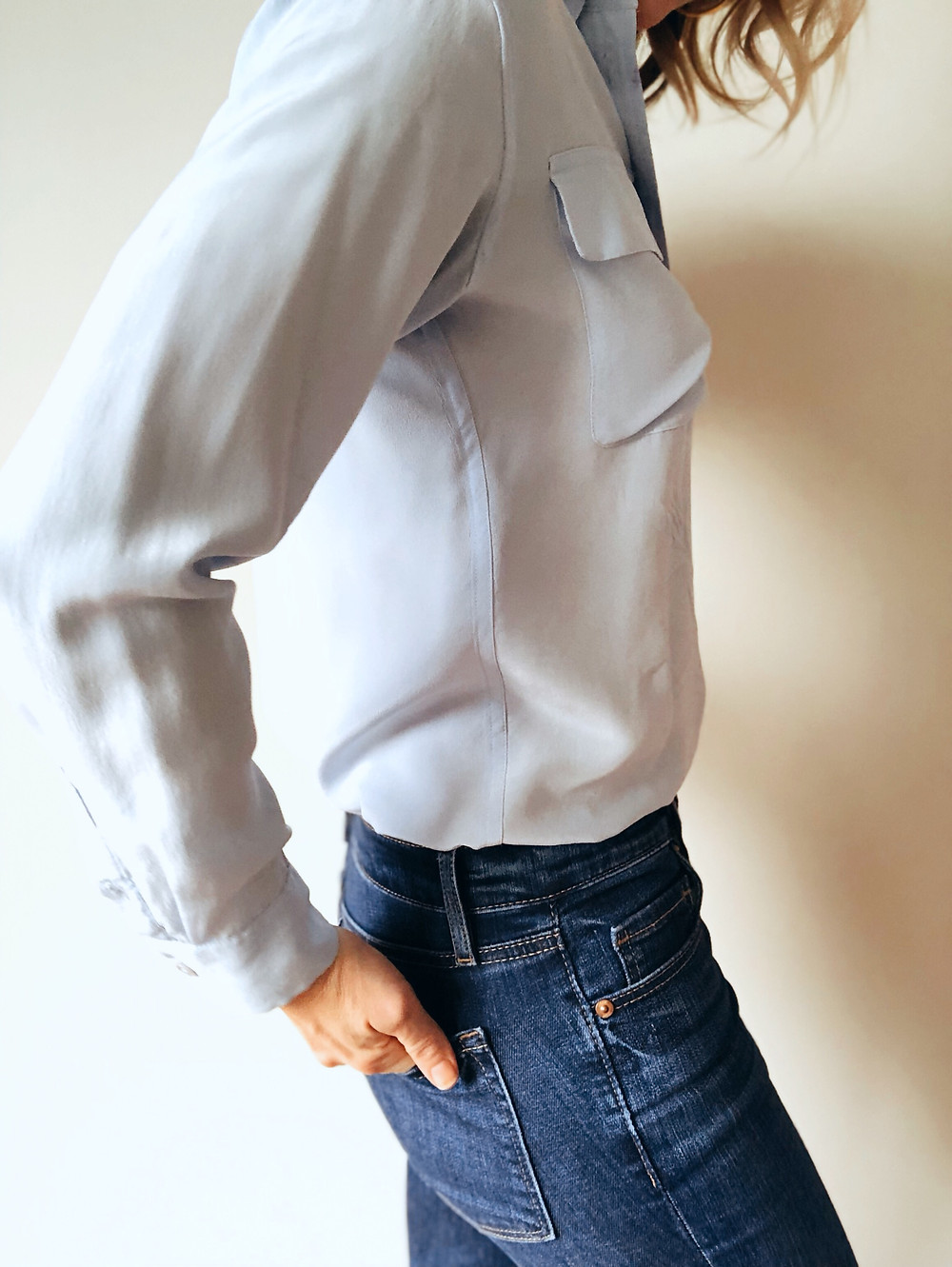 Side view of silk blouse and blue jeans.