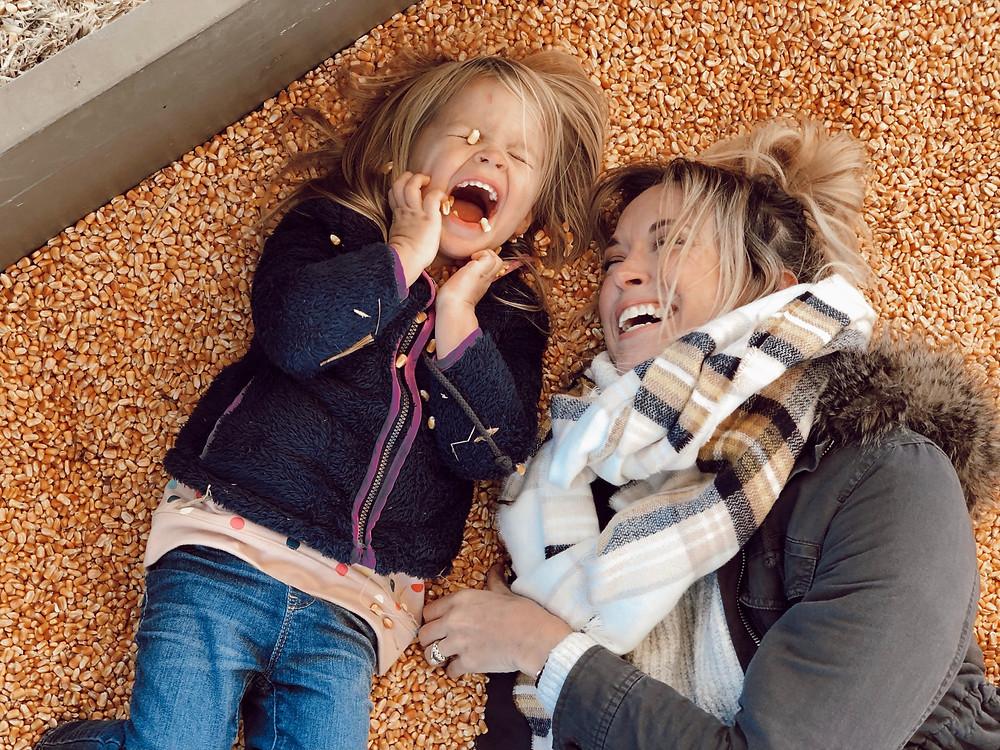 Mommy daughter laugh in corn kernel sandbox at Eliada Home Corn Maze Asheville