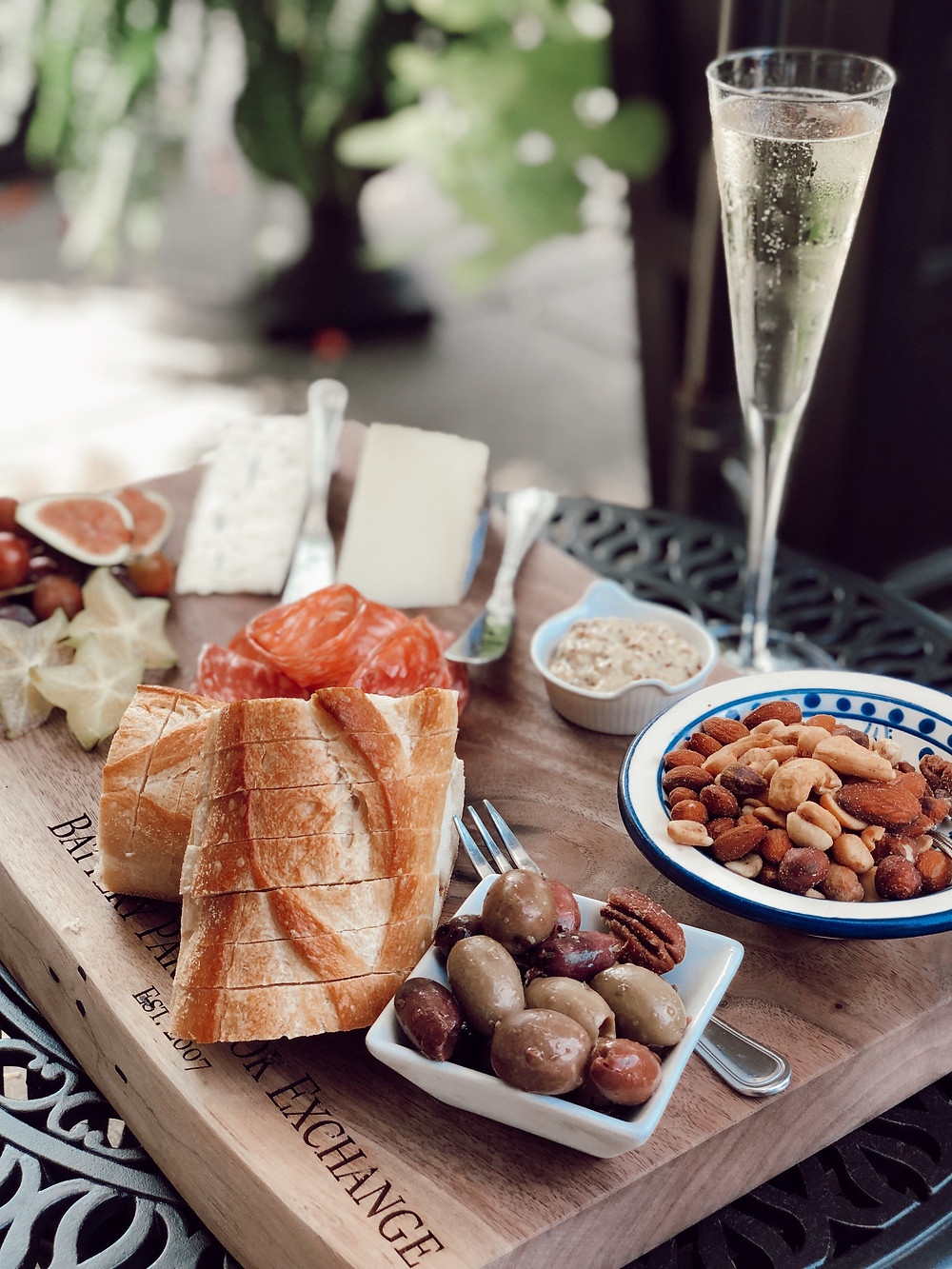 Cheese board, charcuterie, and champagne at an outdoor table at Battery Park Book Exchange and Champagne Bar at the Grove Arcade in Asheville North Carolina. Local travel guide and lifestyle blogger The Tony Townie.