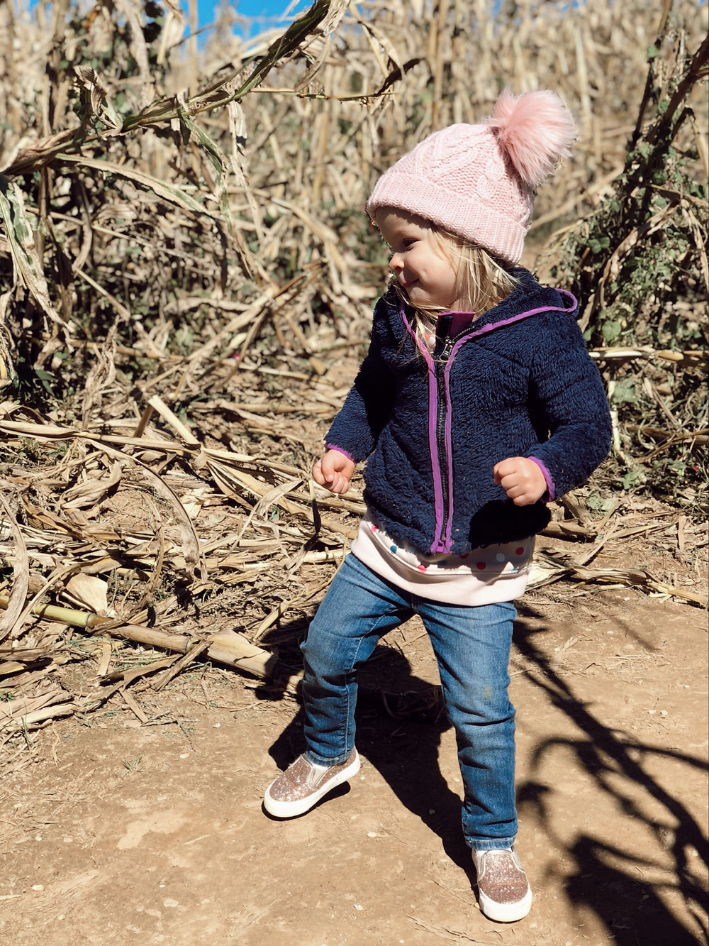Little girl dances in corn field at Eliada Home Corn Maze Asheville