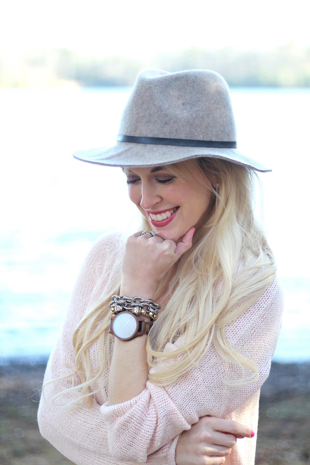 A young mom smiles as she stands by the lake admiring her JORD Wood Watch.