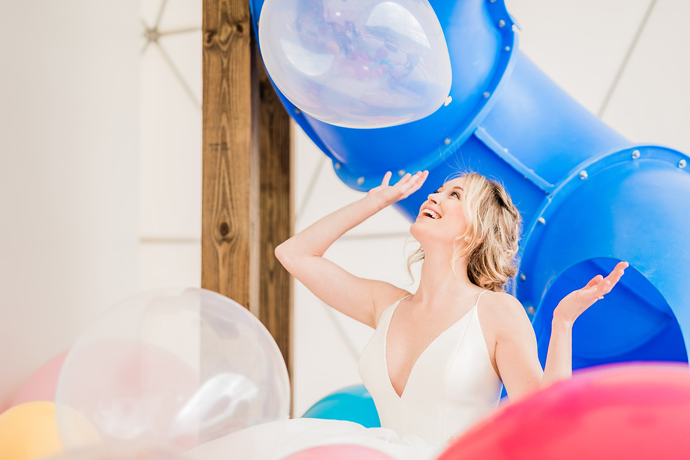 Bride plays with clear balloon during bridal shoot