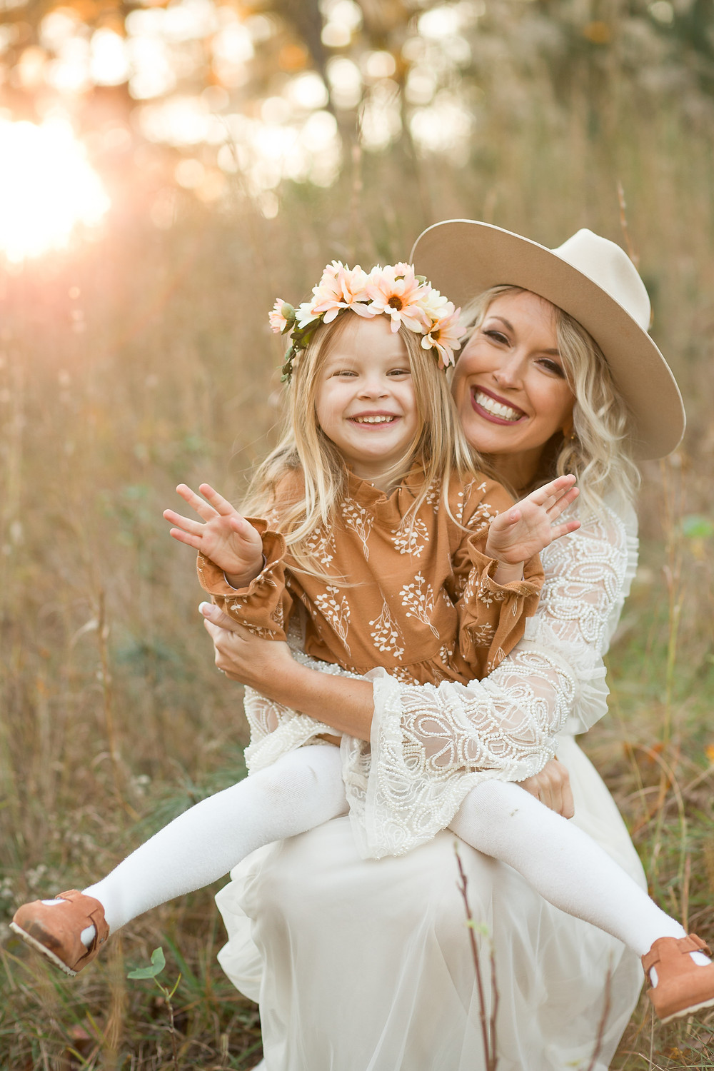 Mom holds smiling daughter in her lap in a grassy field, London Adelaide family photography, Asheville family photographers, tips for planning family photos, lifestyle blog