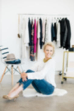 Wardrobe stylist Brooke Williams sits in front of a rolling rack full of fashionable clothing at Engaged Asheville studio.