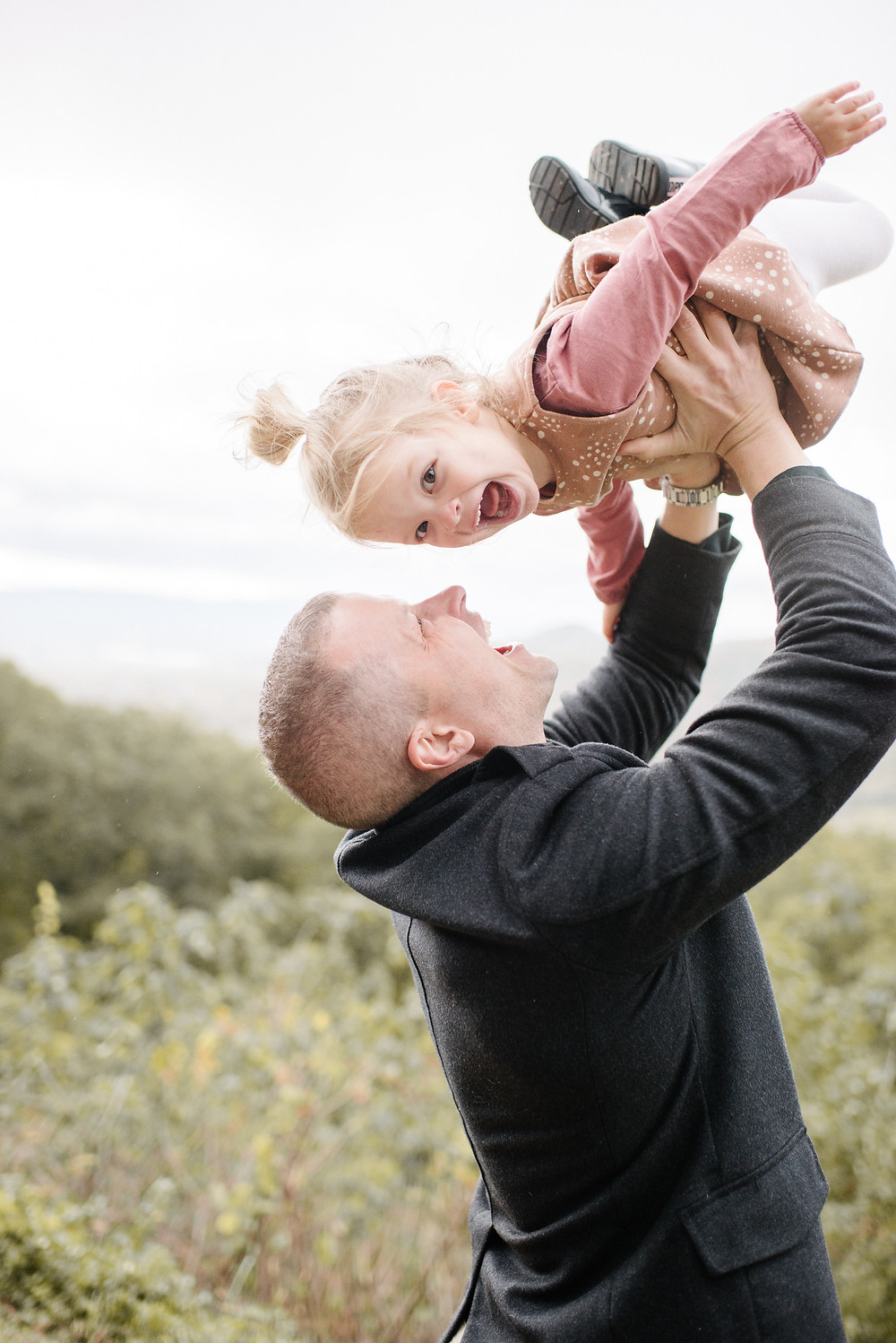 Dad lifts daughter into air.