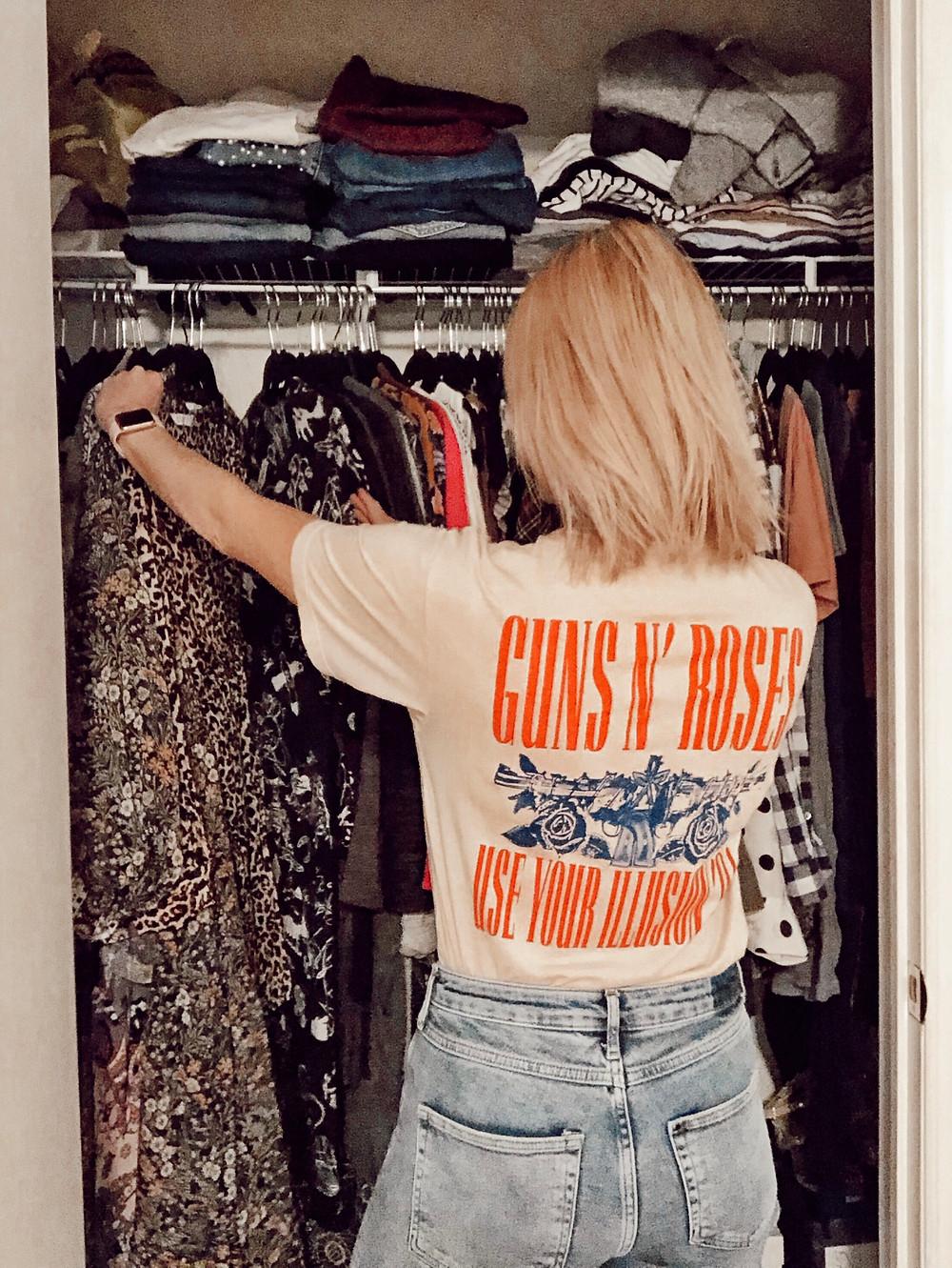 Woman looks through closet while wearing Guns n' Roses t-shirt