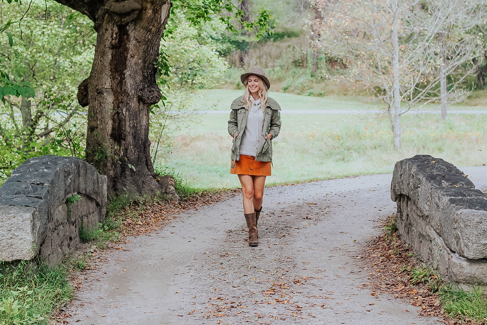 Brooke (The Tony Townie) walks across stone bridge wearing corduroy skirt and olive utility jacket.