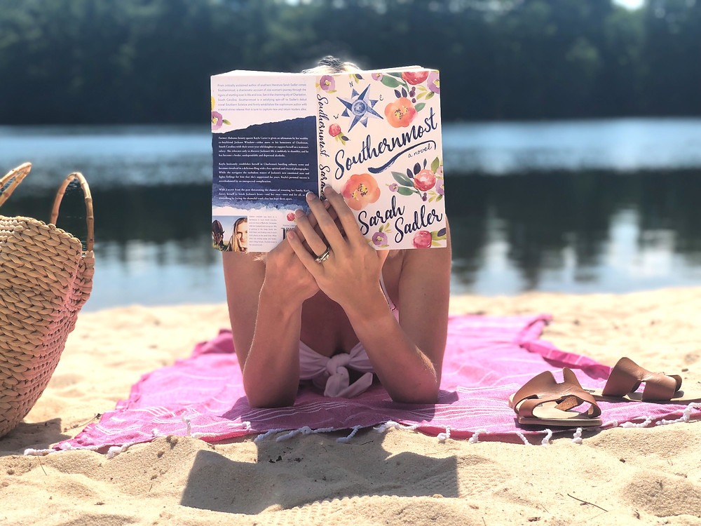 Woman reads Charleston-based novel Southernmost lying on a pink Turkish towel next to a mountain lake.  Summer beach reading list.