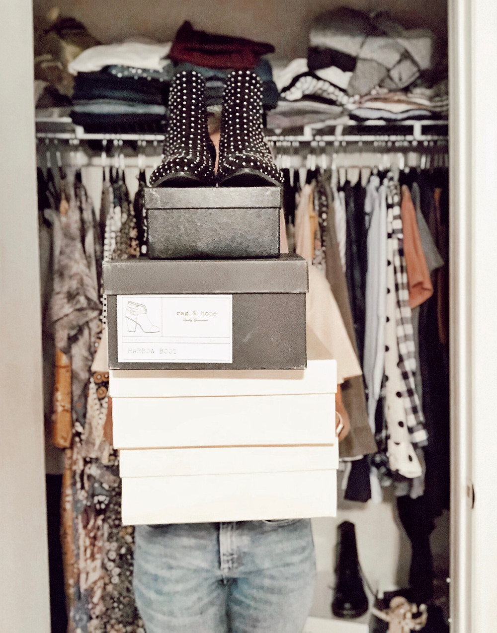 Woman stands in front of closet holding stack of shoe boxes with studded ankle booties on top.