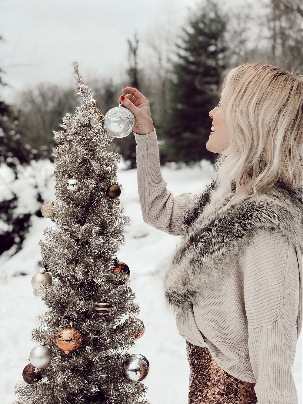 Woman wearing sequin skirt and fur collared sweater stands in snow while decorating a rose gold metallic Christmas tree.