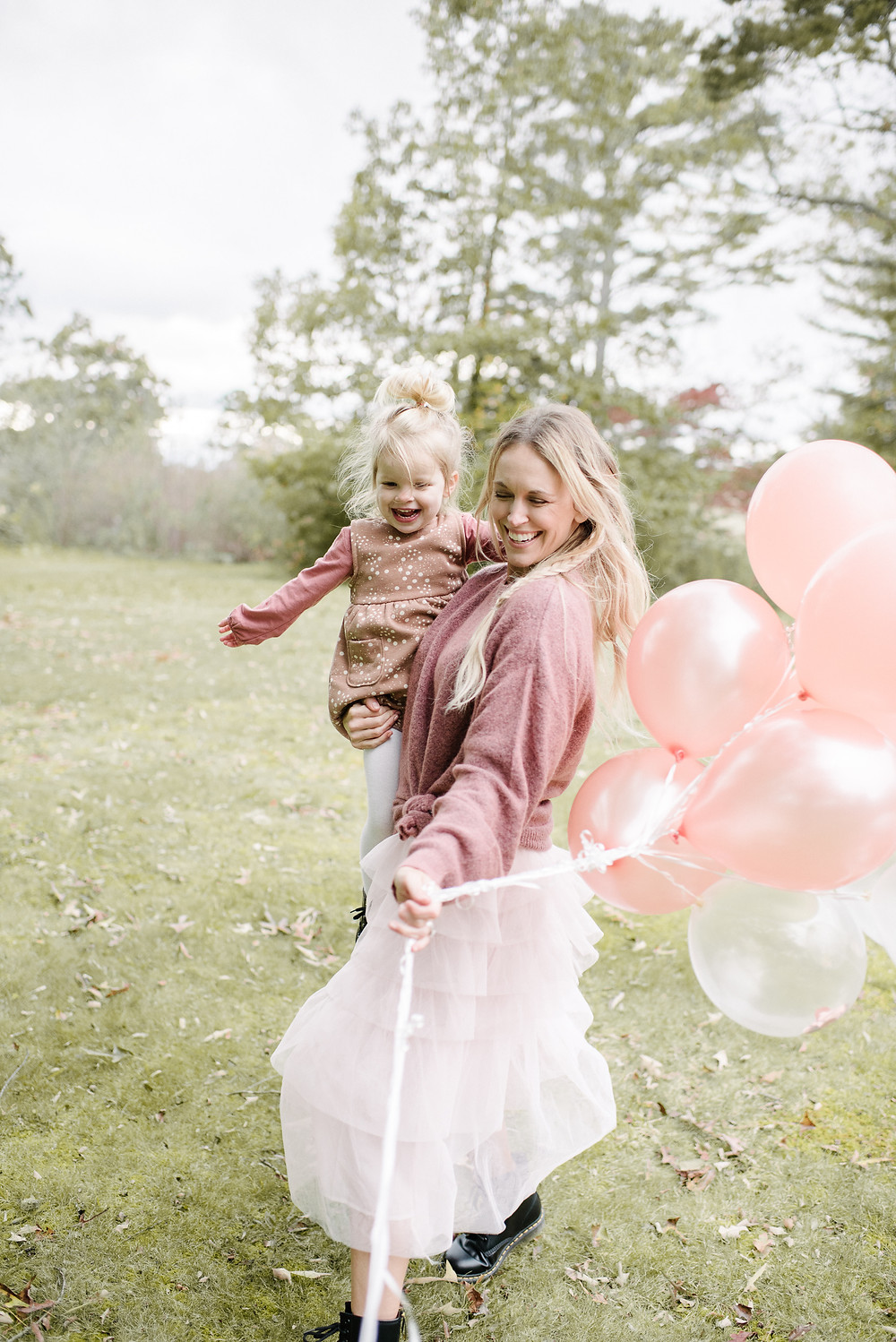 Mom and daughter twirl with pink balloons.