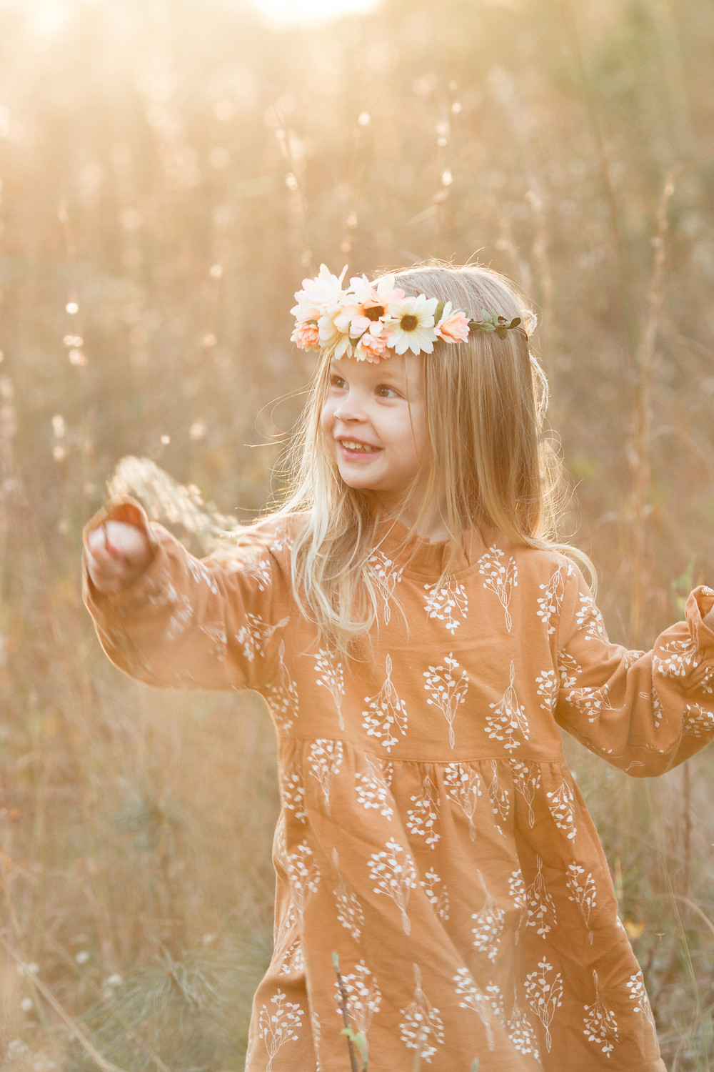 Little girl smiles wearing a flower crown in a grassy field, London Adelaide family photography, Asheville family photographers, tips for planning family photos, lifestyle blog