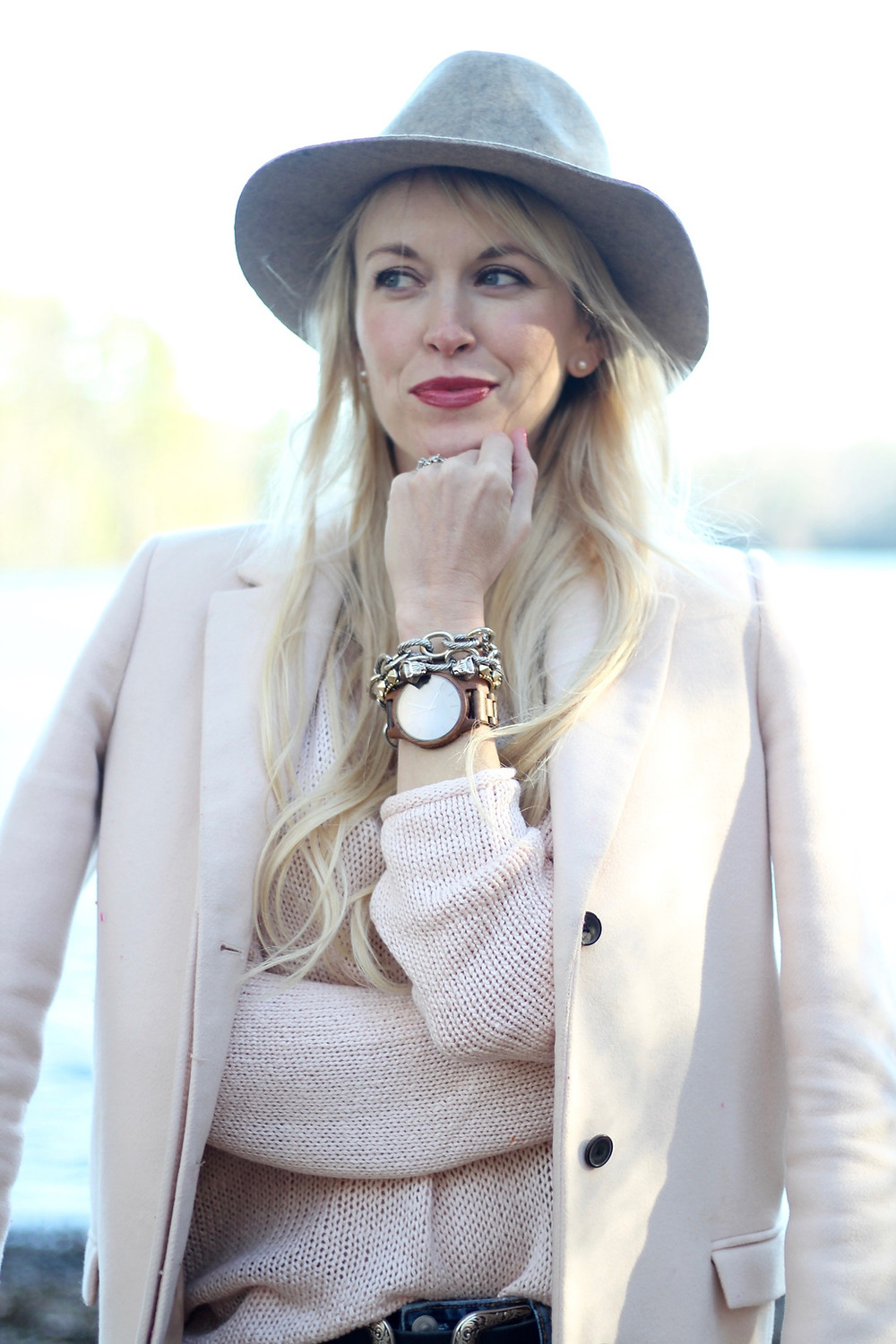 A young mom in a wide brim hat and blush pink winter layers displays her arm paty with a JORD Wood Watch.