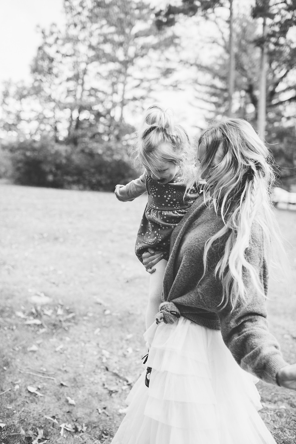 Black and white photo of mom and daughter dancing outside.